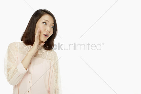 20 24 years : Woman showing a whispering hand gesture