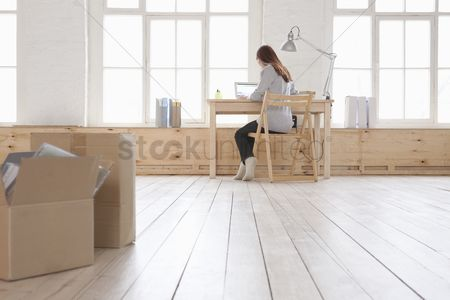 Desk : Woman sits at desk in window area of loft apartment