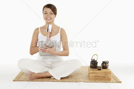 Tea pot : Woman sitting and meditating with digital tablet and credit card