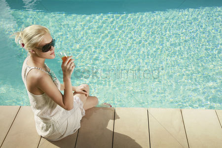 Refreshment : Woman sitting by the poolside holding a glass of juice
