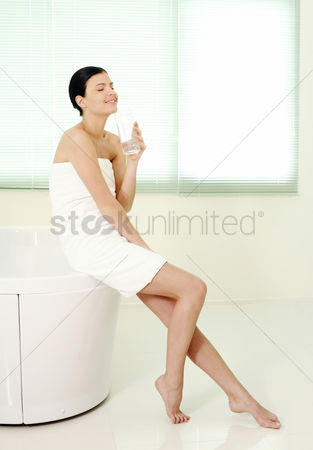 Satisfying : Woman sitting on bathtub ledge holding a glass of water