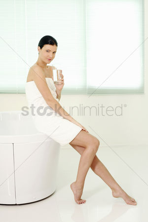 Satisfying : Woman sitting on the bathtub ledge holding a glass of water