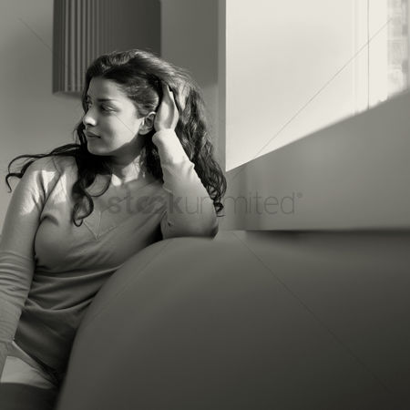 Posing : Woman sitting on the couch daydreaming