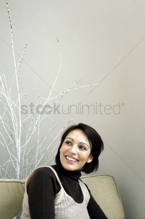 Housewife : Woman sitting on the couch smiling