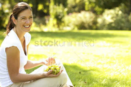 Enjoying : Woman sitting on the field holding green grapes