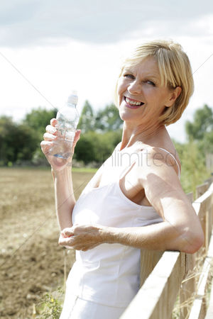 Aging process : Woman smiling at the camera while holding bottled water
