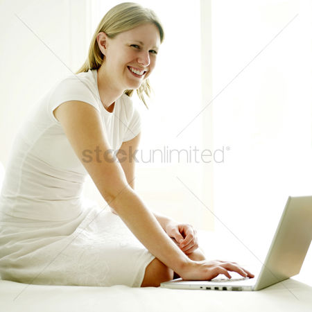 Satisfaction : Woman smiling at the camera while using laptop