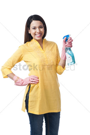 Housewife : Woman spraying with a cleaning fluid