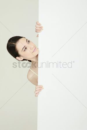 Cardboard cutout : Woman standing behind blank placard smiling and looking down
