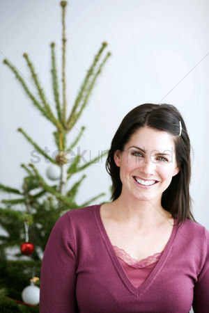 Maturity : Woman standing in front of a christmas tree