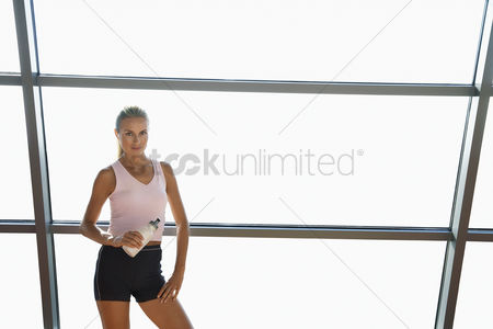 Club : Woman standing with water bottle by window in health club portrait
