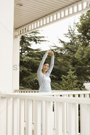 Practising yoga : Woman stretching on the porch