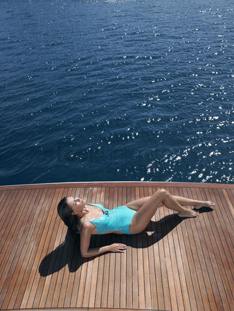 Day off : Woman sunbathing on yacht
