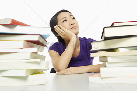Asian : Woman surrounded by books  looking bored