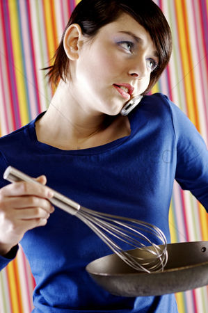 Cellular phone : Woman talking on the phone while cooking