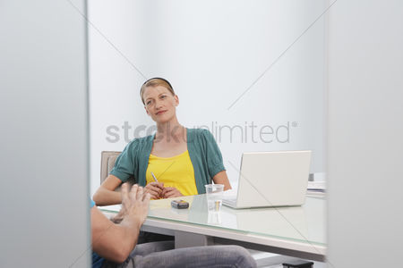 Advice : Woman talking to man  mid section  in office
