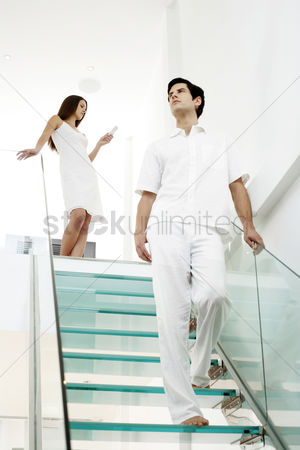 Stairs : Woman text messaging on the mobile phone while her boyfriend is walking down the stairs