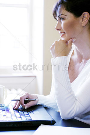 Enjoying : Woman thinking while using laptop