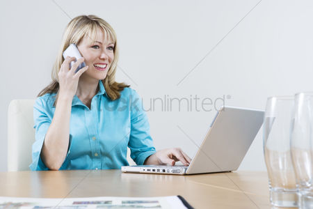 Internet : Woman using cell phone and laptop