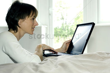 Notebook : Woman using laptop in the bedroom
