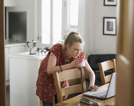Obsessive : Woman using laptop on dining table elevated view