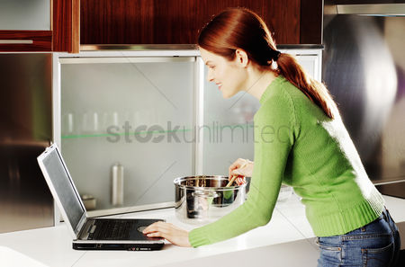 Internet : Woman using laptop while cooking in the kitchen