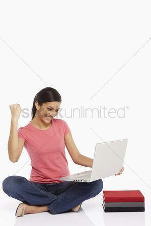 Portability : Woman using laptop while sitting on the floor  cheering