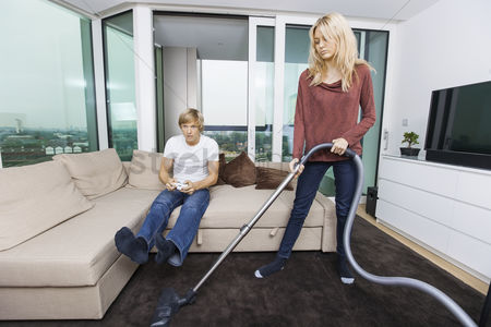 Flat : Woman vacuuming while man play video game in living room at home