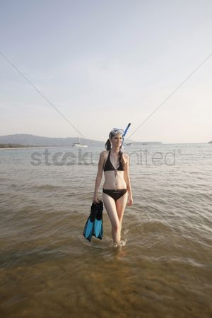 Diving : Woman walking through water  holding flippers