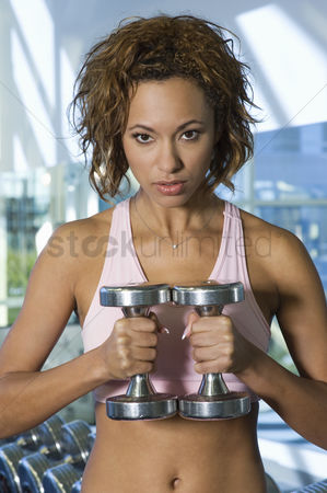 Posed : Woman weightlifting with dumbbells