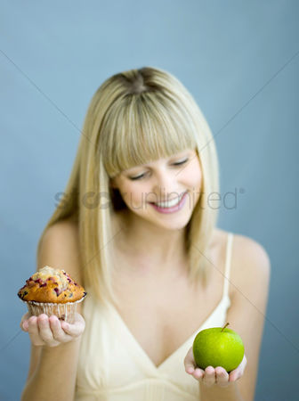 Food  beverage : Woman with a cupcake and green apple