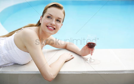 Lying forward : Woman with a glass of red wine relaxing on the pool side