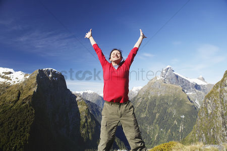 Appearance : Woman with arms raised on top of mountain peak