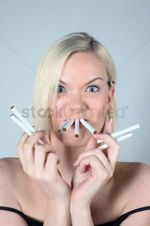 British ethnicity : Woman with cigarettes in her mouth and holding some in her hands