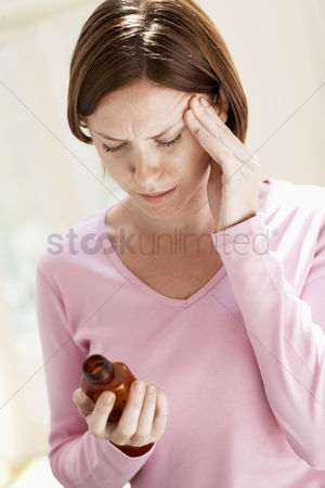 Medication : Woman with headache holding pills touching head