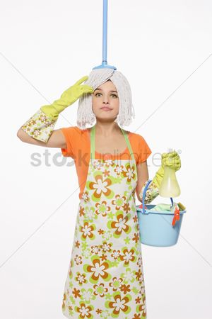 Housewife : Woman with mop on her head carrying a pail of cleaning products