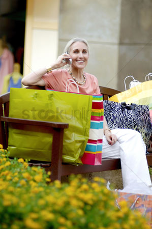 Cellular phone : Woman with paper bags talking on the mobile phone while sitting on the bench