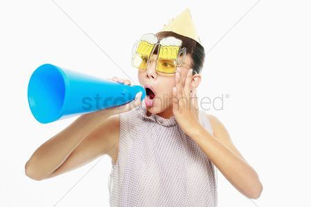 Blowing : Woman with party hat screaming into megaphone