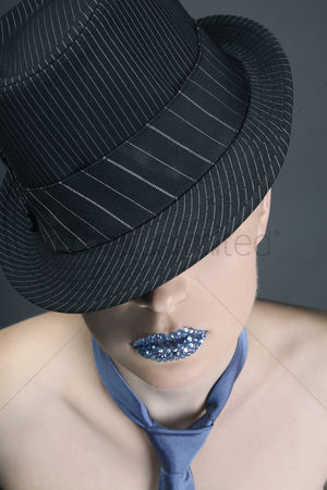 Elegance : Woman with rhinestones on her lips wearing hat and necktie