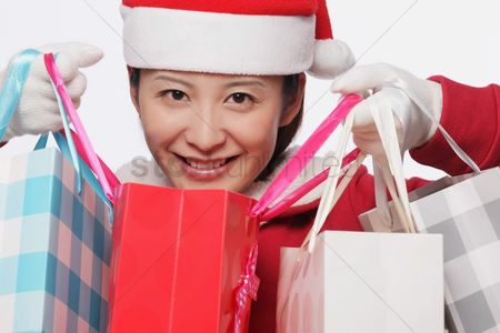 Shopping background : Woman with santa hat carrying shopping bags