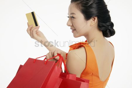 Shopping background : Woman with shopping bags holding up credit card