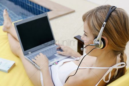 Accessibility : Woman with telephone headset using laptop by the pool side