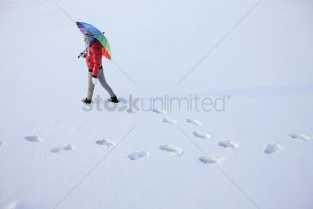 Winter : Woman with umbrella walking on snow