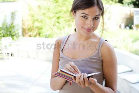 Two people : Woman writing in her organizer