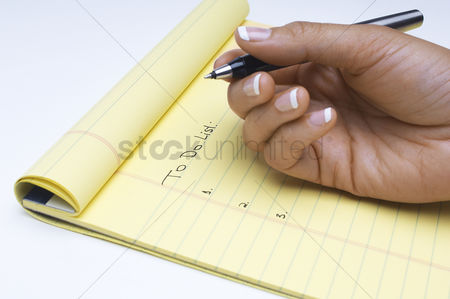 Background : Woman writing list of tasks to do close-up of hand