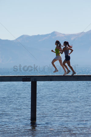 Ponytail : Women running along pier in front of mountains side view