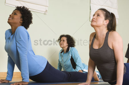 Mature : Women stretching backs in yoga class