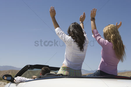 On the road : Women with hands raised in the back of a convertible