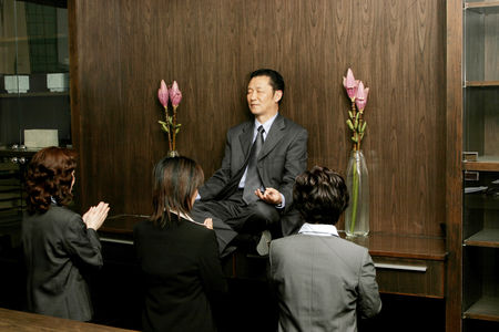 Respect : Women worshipping a businessman who is sitting on the shelf meditating