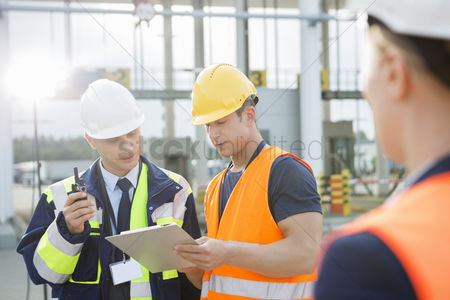 Supervisor : Workers discussing over clipboard in shipping yard